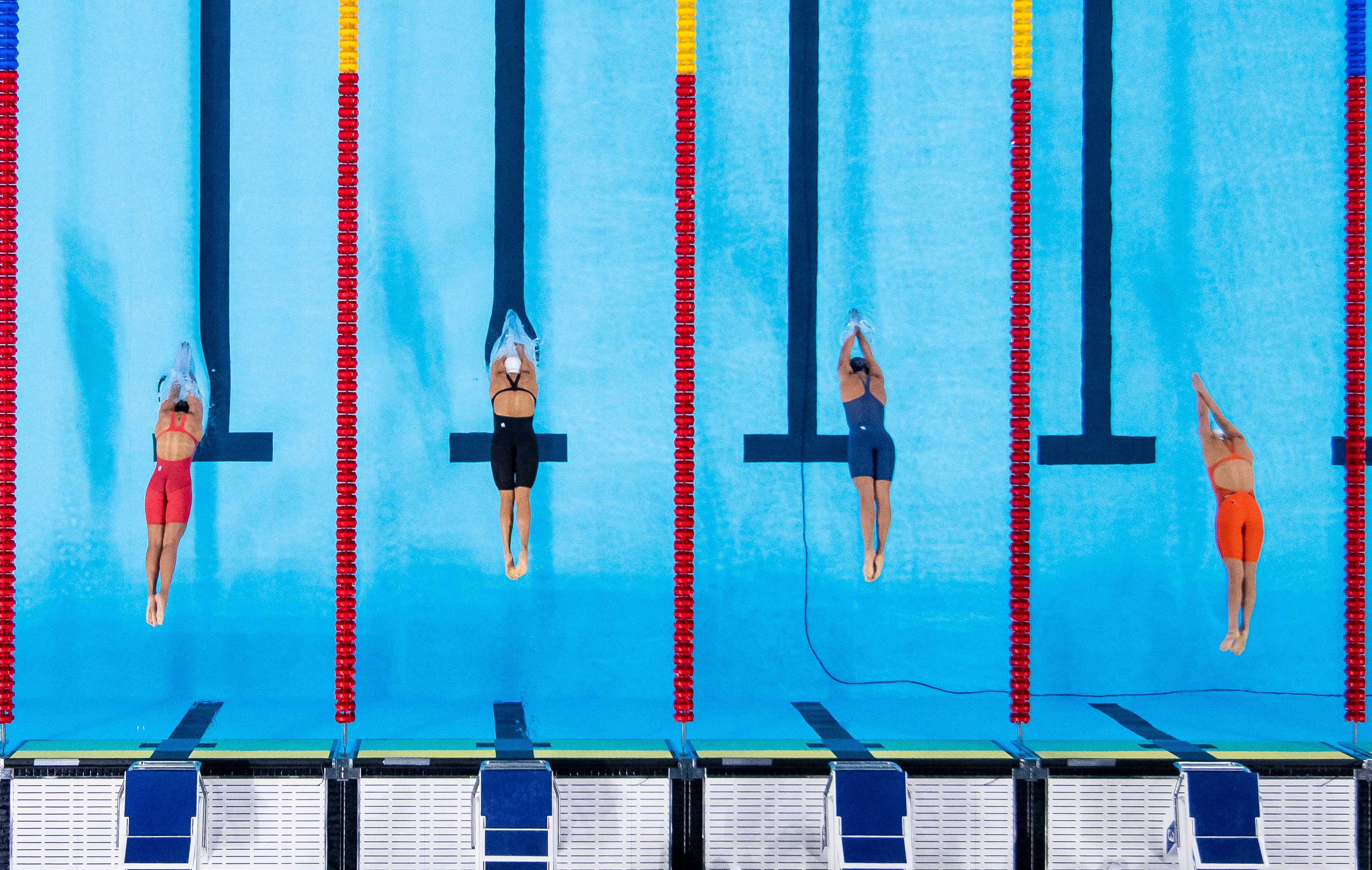 4 swinning athletes are jumping in the pool (top view)